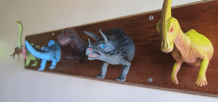 coat rack made from cut in half plastic dinosaurs