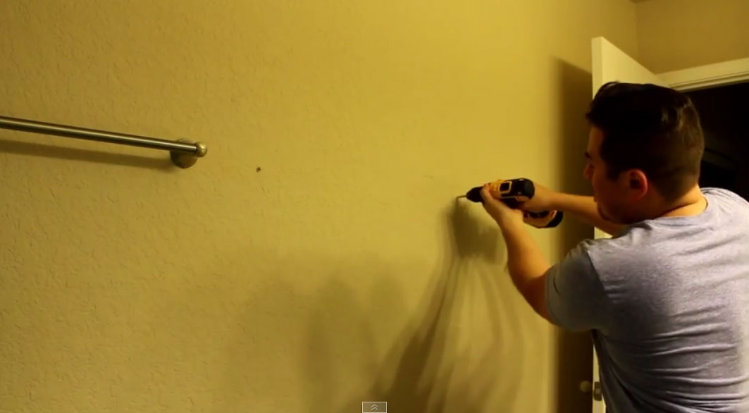 Drilling pilot holes into the wall with a drill